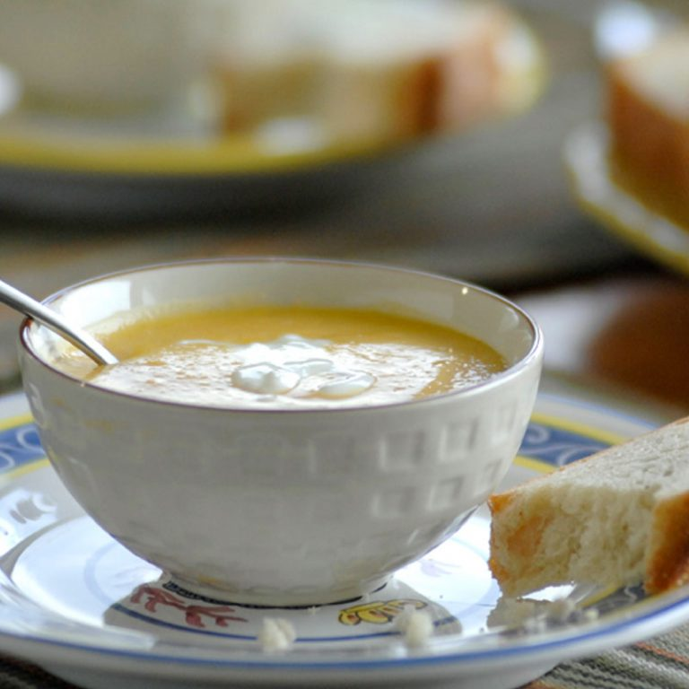A bowl of apple butternut squash soup with yogurt