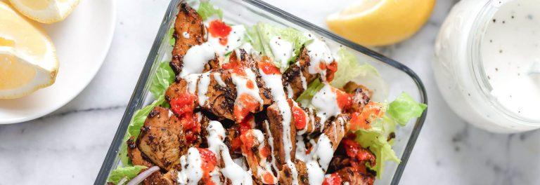Food cart-inspired chicken served over a big salad of lettuce and tomatoes.