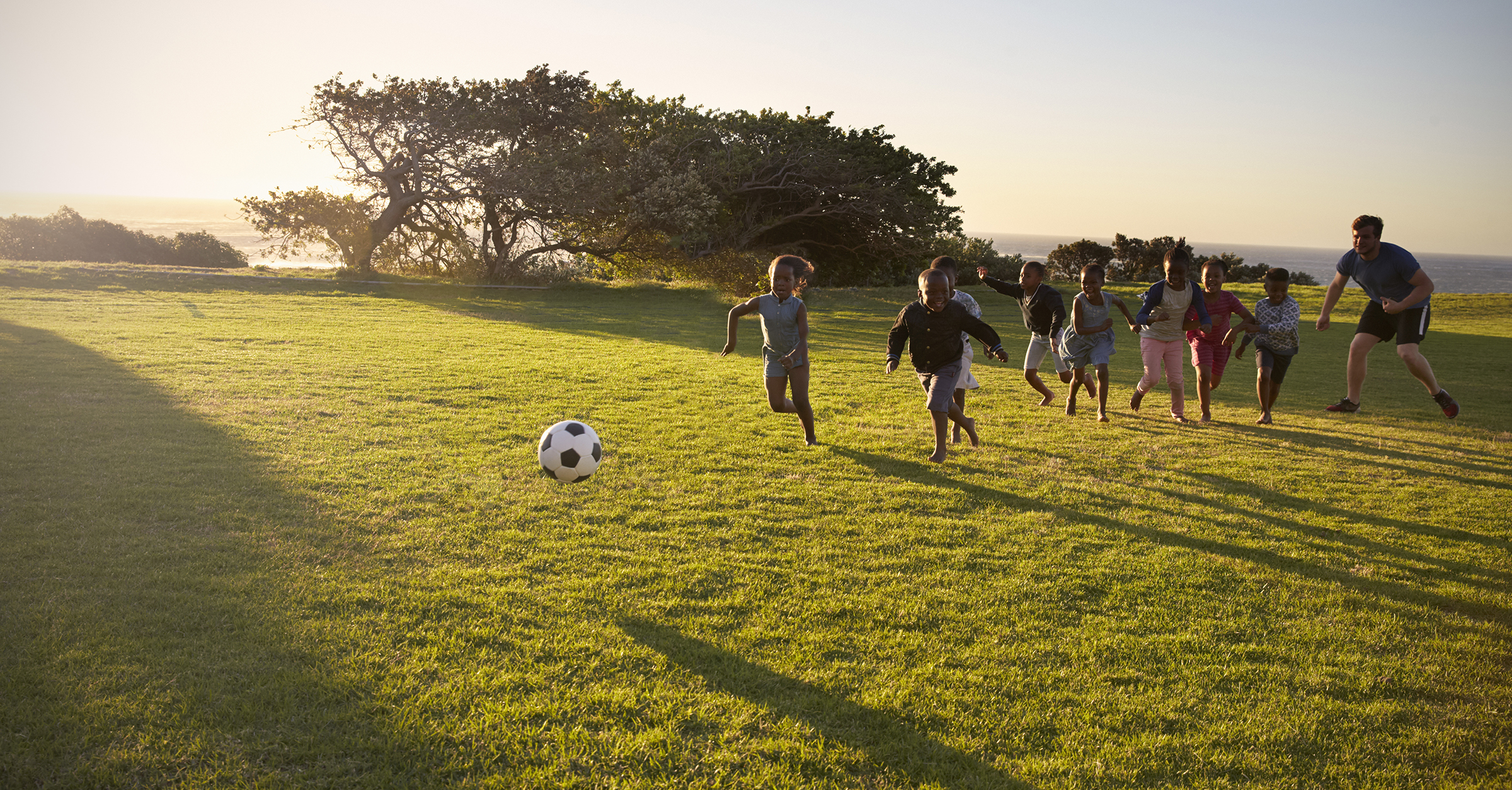 Teacher and elementary school kids play football in a field