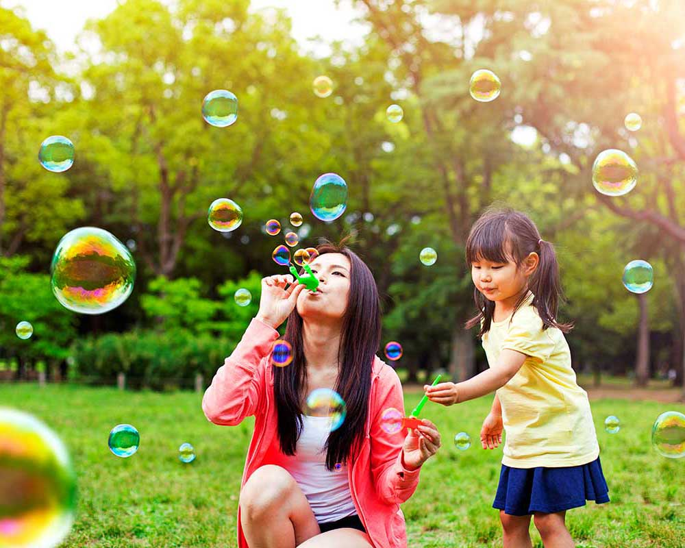 Mom & Daughter Blowing Bubbles In Backyard